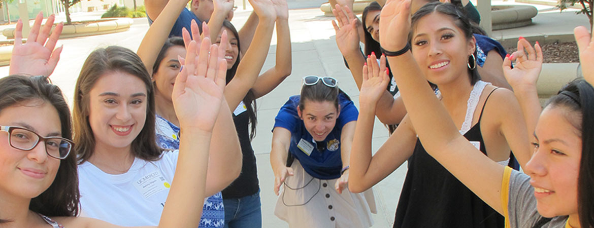 Orientation participants create raised hand tunnel for Orientation Leader